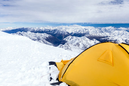 Expedition camping in tent on Mount Elbrus trail to the top, Mountain landscape in autumn or winter in Caucasus Mountains i Russia and Georgia, view from Elbrus(5642m) slopes on Pastuchov Rocks 4700m. Mountain ridge over blue sunny sky